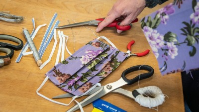 Auf einem Tisch liegt ein fertig genähter Mundschutz mit floralem Muster auf lila Hintergrund sowie diverse Utensilien wie Scheren, Zange, Gummibänder und eine Rolle Draht. (dpa / Frank Rumpenhorst)