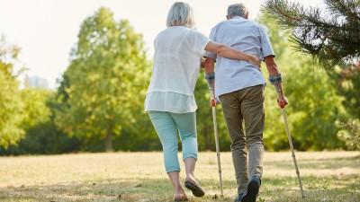Eine Altenpflegerin hilft einem Mann auf Krücken beim Gehen. (EyeEm / Robert Kneschke)