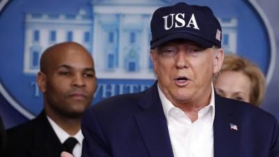 Trump steht in blauer USA-Baseballmütze am Rednerpult im Presseraum des Weißen Hauses. Hinter ihm stehen zwei Männer und eine Frau. (Alex Brandon / AP / dpa)