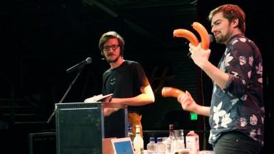 """Während Lukas Diestel (l) aus dem Buch """"Worst of Chefkoch"""" vorliest, zeigt Jonathan Löffelbein Fleischwürste (dpa (Christina Storz))"""