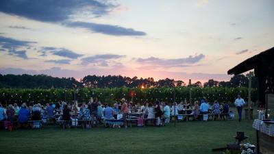 In einem Garten sitzen Menschen zum Essen an einem langen Tisch. (Unsplash / David Todd McCarty)