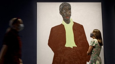 A gallery worker poses with an artwork entitled Untitled by Ghanaian artist Amoako Boafo during a photo call for Modern and Contemporary African Art, comprising over 120 works by 66 artists, at Sotheby's Galleries in central London on October 2, 2020. (Tolga Akmen / AFP)