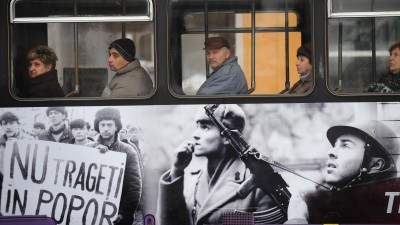 Fahrgäste sitzen in einer Straßenbahn in Timișoara, die mit Fotos der Rumänischen Revolution 1989 beklebt ist  (AFP/ Daniel Mihailescu)