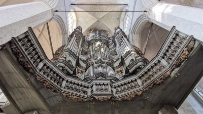 Blick senkrecht von unten nach oben ineiner Kirche, wo über einer Brüstung zwischen mächtigen Steinsäulen die Edelstahl-Pfeifen einer Kirchenorgel hängen. (Stadterneuerungsgesellschaft Stralsund mbH)