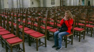 Frau sitzt im Magdeburger Dom inmitten leerer Stuhlreihen und betet.  (imago stock&people)