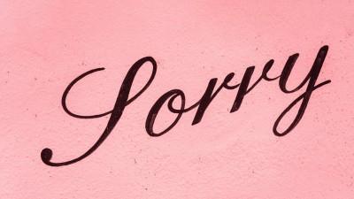 """Auf einer rosafarbenen Hauswand steht in schwarzer Schreibschrift """"Sorry"""" (Unsplash / Nick Fewings)"""