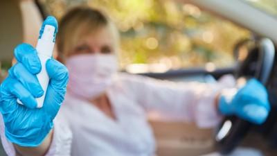 Frau im Auto mit Mundschutz und Desinfektionsmittel (picture alliance / Zoonar.com / Robert Kneschke)