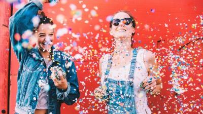 Zwei Frauen stehen vor einer roten Wand und werfen voll Freude Konfetti in die Luft. (EyeEm / Criene Images / Carina König )