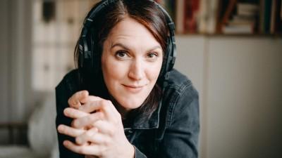 Das Bild zeigt die Musikjournalistin Veronika Schreiegg, die einen Kopfhörer trägt und in die Kamera schaut (Deutschlandradio/Simon Detel)