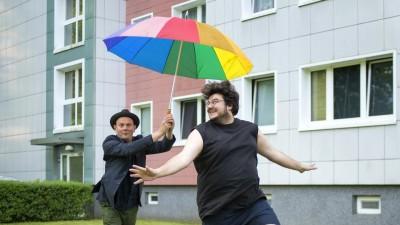 Devid Striesow und Axel Ranisch hüpfend mit einem bunten Regenschirm vor einem Plattenbau. (Deutschlandradio/Dennis Pauls)