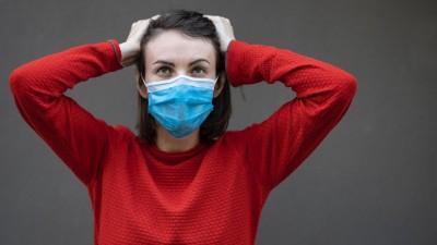 Eine Frau mit Mund- und Nasenschutzmaske fasst sich mit beiden Händen an den Kopf. (Unsplash / Engin Akyurt )