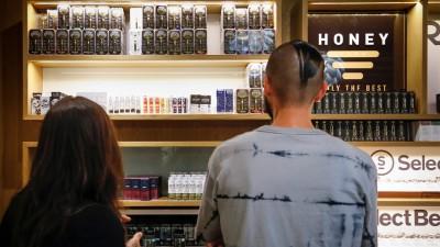Junge Erwachsene stehen vor einer Auslage mit Vaping-Produkten in den USA. (picture alliance / newscom / Howard Lipin)