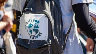 Auf einen Rucksack ist das handgemachte Logo von Fridays for Future gepinnt. (Unsplash / Jasmin Sessler)