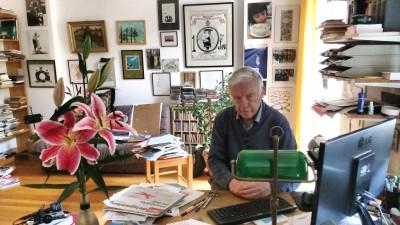 Der Karikaturensammler Koos van Weringh sitzt in seinem Wohnzimmer am Schreibtisch (Deutschlandradio/Sarah Mahlberg)
