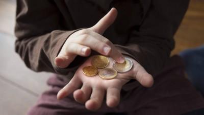Ein Kind, dessen Gesicht man nicht sieht, zählt sein Taschengeld auf der ausgestreckten Hand. (Imago Images/ Photothek/ Ute Grabowsky)