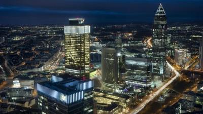 Skyline und Messe in Frankfurt am Main bei Nacht: Bürohäuser mit leuchtenden Fenstern sowie hell erleuchtete Straßen (imago/ imagebroker/ Andreas Mechmann)