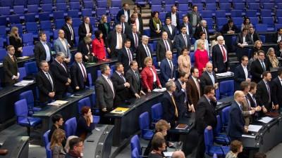 Abgeordnete von SPD und CDU stehen vor ihren Plätzen im Bundestag (dpa / Soeren Stache)