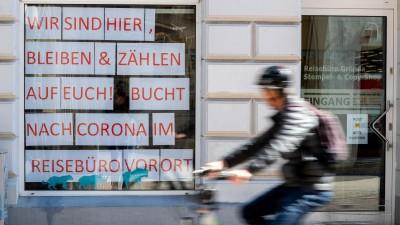Ein Radfahrer fährt am Schaufenster eines Reisebüros vorbei. Nach wochenlanger Zwangsschließung wegen der Corona-Schutzmaßnahmen dürfen vom 20.04.2020 an Geschäfte des Einzelhandels wieder öffnen. (picture alliance / dpa ZB / Jens Büttner)