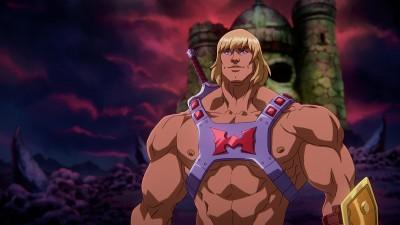 """Still aus der Animationsserie """"Masters of the Universe: Revelation"""": Ein äußert muskulöser Mann mit blonden Haaren und einem außer etwas Rüstung nackten Oberkörper, bewaffnet mit einem Schwert, steht vor einer Burg und einem rötlich-dunkel verfärbten Himmel. (Netflix)"""