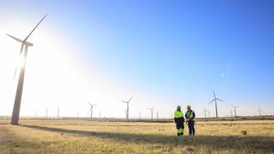 Zwei Männer in Arbeitskleidung stehen auf einer Wiese vor einer Windkraftanlage. Symbolfoto. (imago images / Westend61)