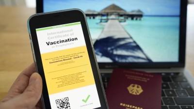 Symbolfoto: Digitaler Impfass und Reisepass vor Fernweh-Motiv auf einem Laptop. (IMAGO / Political-Moments)