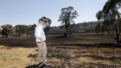 Der australische Premierminister Scott Morrison steht auf verbranntem Boden. Im Hintergrund sind durch den Brand leicht beschädigte Bäume zu sehen. (www.imago-images.de)