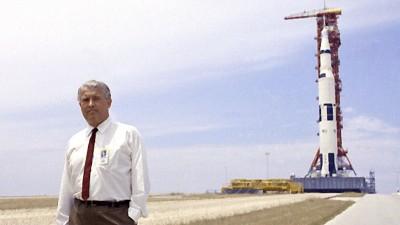 Wernher von Braun (1912-1977) am 1. Juli 1969 auf einem freien Feld,im Hintergrund eine Rakete in ihrem Startgestell. (picture alliance / Everett Collection)