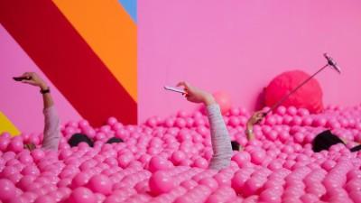 Besucherinnen machen im Supercandy Pop-Up Museum in einem Bällchenbad Selfies.  (dpa/ Rolf Vennenbernd)