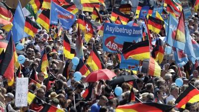 """Das Bild zeigt zahlreiche Anhänger der AfD auf einer Kundgebung gegen die Politik der Bundesregierung in Berlin. Zu sehen sind viele Deutschlandflaggen und Fahnen mit dem AfD-Parteilogo. Auf einem Banner steht zu lesen """"Asylbetrug beenden"""". (dpa-bildfunk / AP / Markus Schreiber)"""