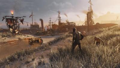 """Die Szene aus dem Spiel """"Metro: Exodus"""" zeit zwei ungeheuerähnliche Gestalten, die den Abhang zu einem Industrieschrottplatz herunterlaufen  (Koch Media)"""