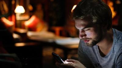 Während ein junger Mann auf sein Smartphone schaut, beleuchtet das Display sein Gesicht. (Unsplash / Eddy Billard )