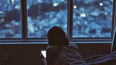 Eine junge Frau liegt bäuchlings im Bett und schaut auf ihr Smartphone. (unsplash / Tony Lam Hoang)