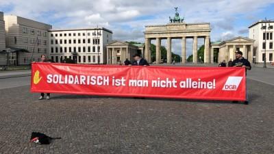 """Demonstranten tragen ein Banner mit der Aufschrift """"Solidarisch ist man nicht alleine"""" vom Deutschen Gewerkschaftbund vor dem Brandenburger Tor in Berlin (Deutschlandradio/S. Engelbrecht)"""