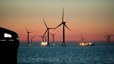 Mehrere Windräder stehen in der Ostsee vor der Insel Rügen. Der Himmel strahlt rötlich. (dpa/Stefan Sauer)