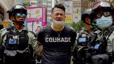"""Ein Demonstrant wird in Hongkong von zwei Polizisten abgeführt. Auf dem T-Shirt des Verhafteten ist """"Courage"""" zu lesen. (Picture Alliance / dpa / AP / Vincent Yu)"""