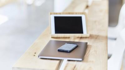 Mobile Endgeräte liegen auf einem Holztisch. (imago images / Westend61)