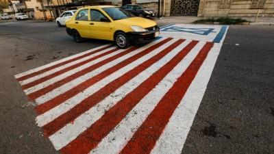 Ein Auto fährt über eine Flagge der USA und einer Flagge von Israel, die auf die Straße gemalt wurden. (dpa/AP/Ameer Al Mohmmed)