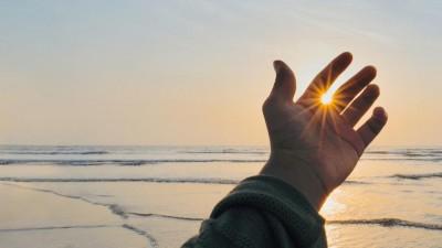 Eine Hand vor der untergehenden Sonne am Meereshorizont (Unsplash / Santosh Verma  )