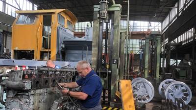 In einer Fabrikhalle steht ein Arbeiter an einer Lokomotive mit einem orangen Fahrerhaus (Sabine Adler/ Deutschlandradio)