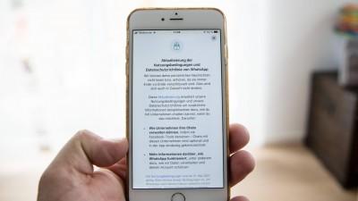 Eine Person hält eine Handy in der Hand, auf dem Display vom Handy sind die neuen Nutzungsbedingungen, AGBs, von dem Messenger WhatsApp zu sehen sind (IMAGO / Fotostand)
