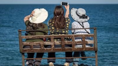 Drei Touristinnen sitzen in Antalya auf einer Bank und blicken aufs Meer. (imago / ZUMA Press)