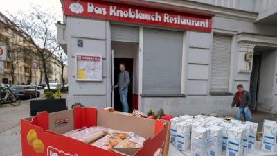 Der Besitzer des Restaurants Knofel in der Wichertstraße in Berlin-Prenzlauer Berg verschenkt wegen der Schließung seine verderblichen Lebensmittel vor seinem Geschäft. (imago images/Seeliger)