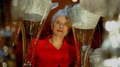 Schriftstellerin Sara Paretzky in rotem Kleid, im Vordergrund sehr groß zwei Sektgläser, in deren Mitte ist die Autorin zu sehen. (imago  / ZUMA Press)