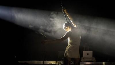 Arca bei einem Auftritt auf der Bühne mit dem Rücken zur Kamera, in einem Lichtstrahl mit Nebel (imago images / Agencia EFE / Quique García)