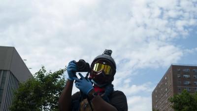 Eine Person mit Helm, Schutzbrille und Kamera dokumentiert in New York eine Demonstration gegen Polizeigewalt (imago images/ZUMA Wir/Dan Herrick)
