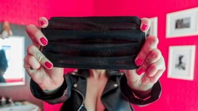 Eine Sexarbeiterin verdeckt mit einer Mund-Nasen-Maske an ihrem Arbeitsplatz ihr Gesicht. (picture alliance / dpa / Markus Scholz)