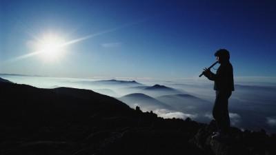 Symbolbild Musik und Natur: Silhouette eines Mannes, der in einer Gebirgslandschaft auf einem Gipfel Flöte spielt. (picture alliance / Michael Coyne)
